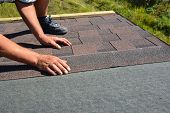 Roofer Hands Laying Asphalt Shingles On House Construction Roof. Roofing Construction With Asphalt S poster