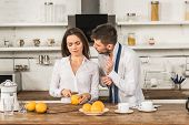 Boyfriend Buttoning Cuff And Girlfriend Cutting Oranges In Kitchen, Social Roles Concept poster