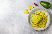 Fresh Guacamole Sauce In Glass Bowl And Mexican Corn Chips poster