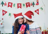 Asia Lover Girlfriend Kiss Cheek And Give Christmas Gift At Xmas Party,asia Girl Friends Wear Santa  poster