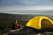 Girl Relaxes Meditating Near Yellow Tent. From The Cliff Overlooking The Mountains And The Lake. Thi poster