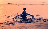 Silhouette of small  boy, kid, sitting alone on the beach at sunset time. kid sitting isolated on a  poster