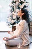 Pregnant woman meditating at home near beautiful decorated Christmas tree, sitting in lotus pose wit poster