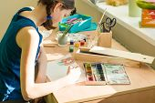 Teenage Girl At Home Is Engaged In Creativity, Drawing Watercolor At A Table In Room. Child Creativi poster