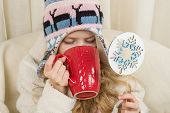 Little Girl Sitting At Home In The Chair, In Knitted Hat With Christmas Ornament With Cup Of Hot Dri poster