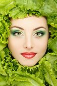 woman beauty face with green fresh lettuce leaves frame