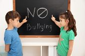 Little children near chalkboard with words No to bullying indoors poster