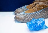 Crumpeled Blue Shoe Covers Mans Shoes In Medical Shoe Covers poster