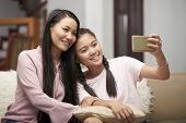 Beautiful Asian Adult Woman With Charming Teen Girl Sitting On Sofa And Taking Selfie With Phone poster