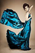stock photo of wind blown  - Beautiful young woman holding a blue silk dress in a fashion portrait - JPG