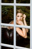 image of snob  - portrait of a beautiful fashion model lying on the couch looking out the window - JPG