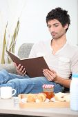 picture of glorify  - Man reading book whilst eating breakfast - JPG