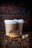 Disposable Take-out Mock-up Paper Cups With Coffee Beans On Wooden Background poster