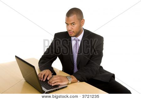 Serious Businessman At Desk Working On Laptop