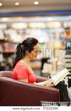 young woman reading a book in bookstore