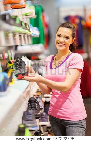 happy young woman choosing sports shoes to buy in store