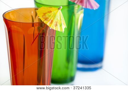 Colored drinking glasses with umbrellas on white background