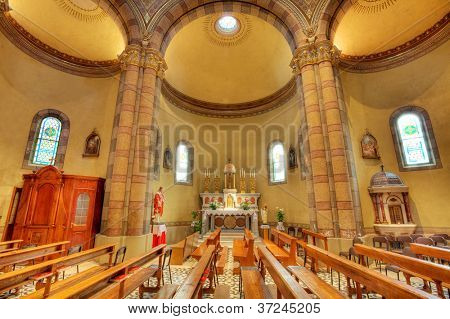 Pews and altar among columns in Madonna Moretta catholic church in Alba, Italy.