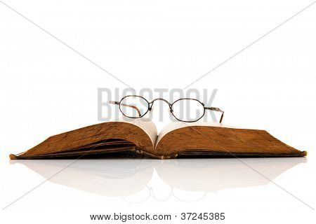 Old open book with glasses isolated over white background