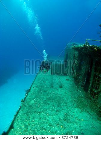 Diver Swimming Along Side A Sunken Shipwreck