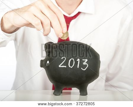 businessman putting money on a piggy bank with a year 2013 drawing