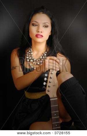 Hispanic Female Rocker With Her Guitar