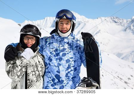 Smiling couple in sport suits and helmets stand with snowboard and skis on mountain.