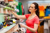 stock photo of department store  - young female sportswear shop assistant working in store - JPG