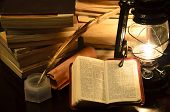 foto of inkpot  - a bible surrounded by books in a lamp light