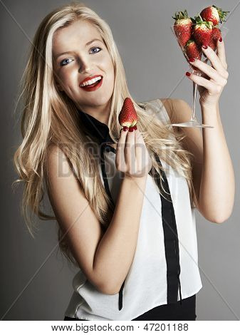 Pretty blonde girl holding glass of Strawberries