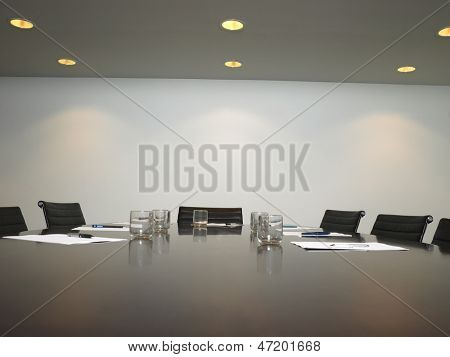 Conference room with arranged water glass and documents at table