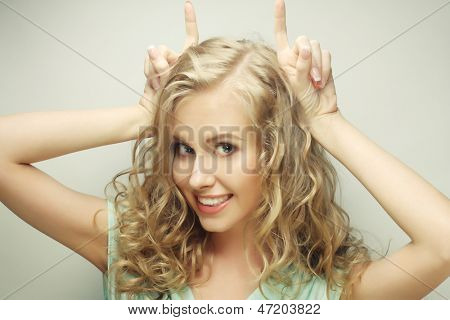 Funny portrait of beauty girl (she is making horns or big bunny ears from her hands), isolated on white