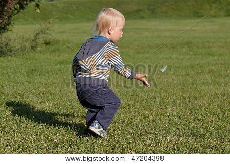 Little boy running on the grass