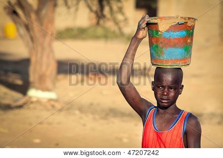 Unidentified Boy Carrying Clay In Wooden Vessel On His Head, In