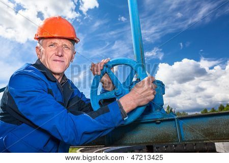 Caucasian Mature Worker With Fitting Valve Against Blue Sky