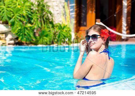 beautiful girl in sunglasses with hibiskus in luxury pool