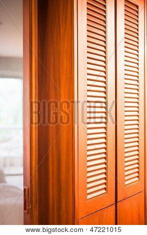 Armario de madera con espejo partición entre el dormitorio y baño