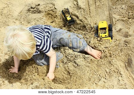 Child Playing Trucks In Sandbox