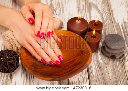 Mãos de mulher macia com unhas coloridas