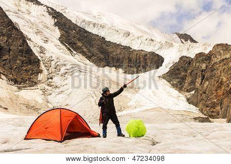 Os custos de alpinista no glaciar perto da tenda