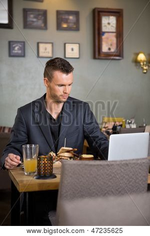 Young business man using laptop while having sandwich in coffeeshop