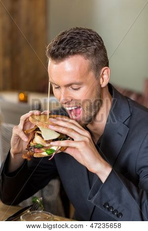 Closeup of young businessman eating sandwich in coffeeshop