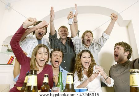 Group of friends watching television and celebrating in living room