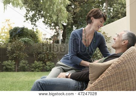 Happy loving woman sitting on man's lap in lawn
