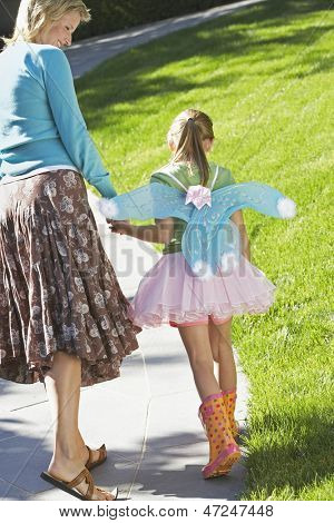 Rear view of happy mother with daughter in fairy costume walking on path at park