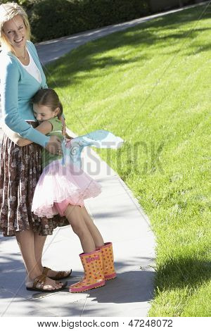 Young girl in fairy costume embracing mother on path at park