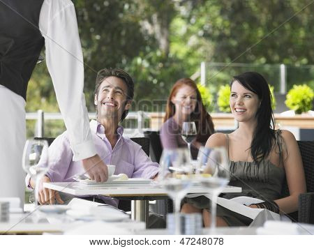 Waiter serving coffee to young couple with woman in background at cafe