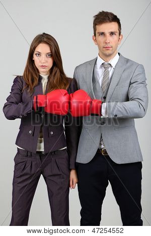 Young business people in boxing gloves on grey background