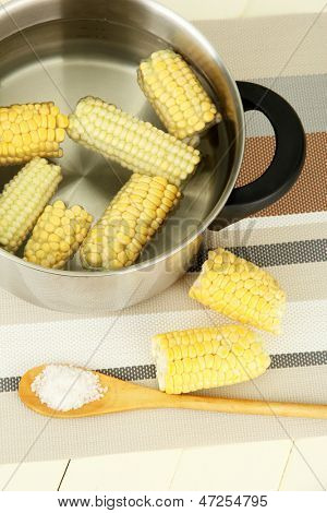 Boiled corn in pan, on wooden  table, on wooden background