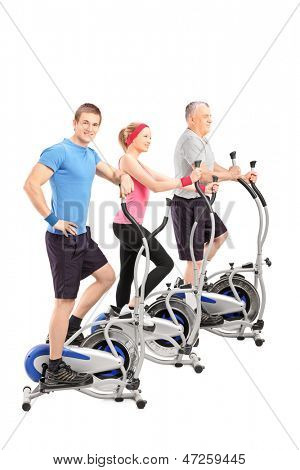 A studio shot of three people working on a cross train machine isolated against white background